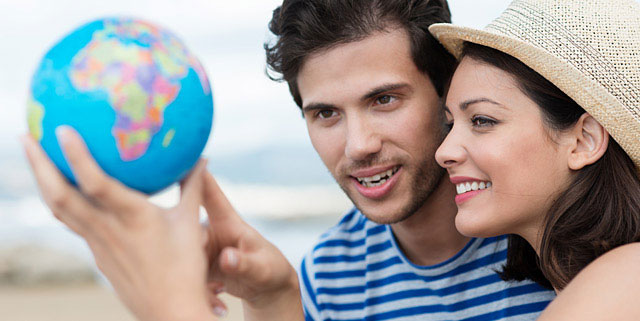 Man and woman looking at a globe
